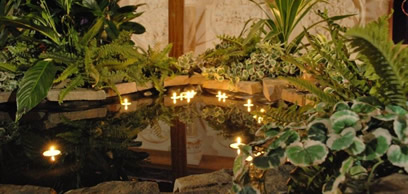 Candles float in the pond before the altar.